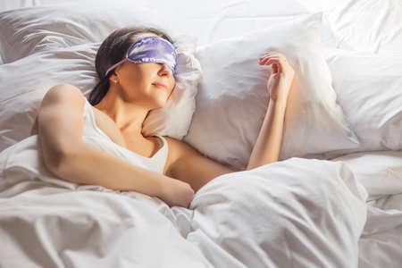sleep well: Woman sleeping in bed with en eye mask