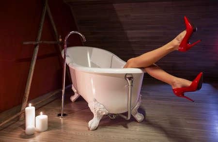 tacones rojos: La mujer en zapatos de tacón alto rojas en el baño Foto de archivo