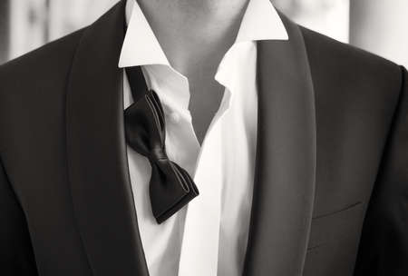 Close-up photo of man in tuxedo with open shirt and loose bow tie