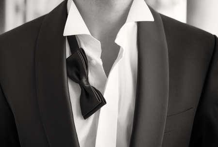lazo negro: Fotos de primer plano del hombre en smoking con la camisa abierta y pajarita suelta