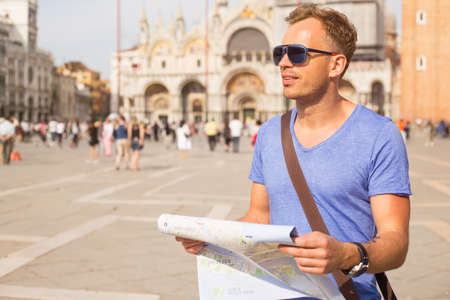 europe travel: Young man holding city map