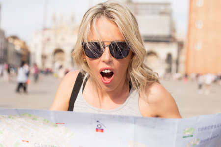 angry blonde: Surprised woman looking at map