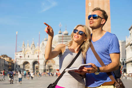 Couple reading tourist guide and sightseeing in Venice