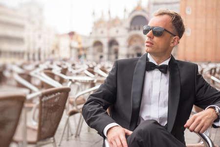 outdoor photo: Portrait of handsome confident man in tuxedo