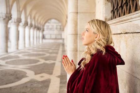 Woman in red cloak pray