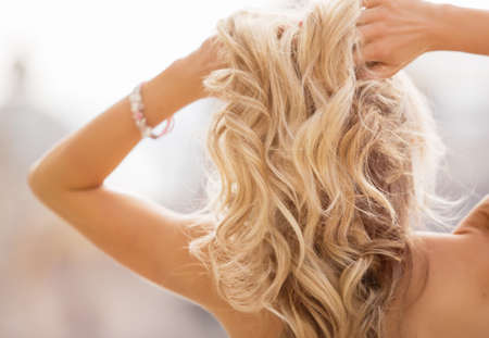 cabello rubio: Mujer rubia que lleva a cabo sus manos en el cabello Foto de archivo