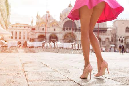 skirts: Mujer de moda con falda de color rosa y zapatos de tacón alto en la plaza San Marco en Venecia