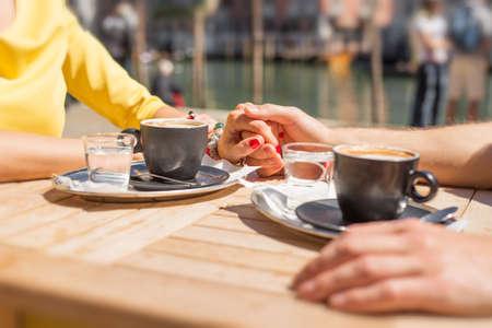 manos entrelazadas: Pareja de la mano y tomar café en café al aire libre