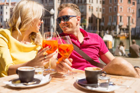 spritz: Young cheerful couple drinking Aperol Spritz cocktail in cafe