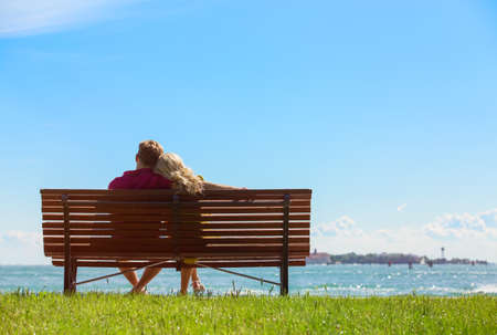 siluetas de enamorados: Pareja sentada en el banco de un parque