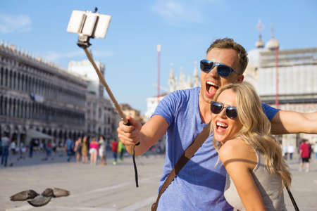 Funny tourist couple making selfie with selfie stick Stockfoto