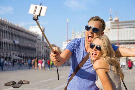 haciendo el amor: Selfie pareja toma tur�stica divertido con el palillo selfie Foto de archivo