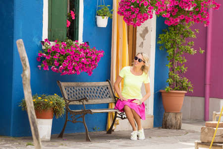 girls youth: Woman sitting on bench in streets of Burano island, Venice Stock Photo