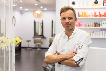 stylist: Portrait of handsome hairdresser in hair salon Stock Photo