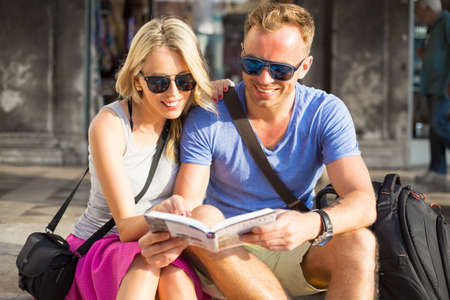 tourist guide: Couple traveling and reading tourist guide book