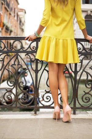 mujeres de espalda: Señora en vestido amarillo de pie en el puente Foto de archivo