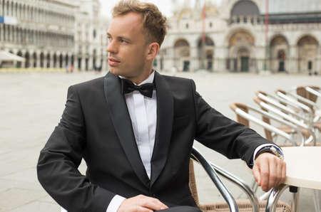 modelos hombres: Hombre en smoking que se sienta en la plaza de San Marcos en Venecia