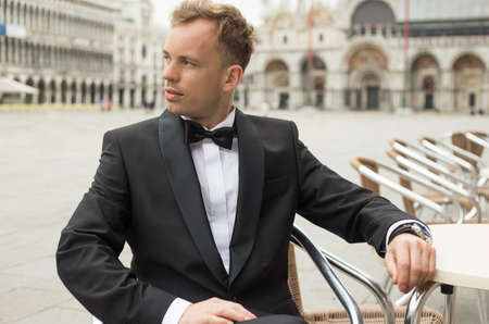 male fashion model: Man in tuxedo sitting in St Marks Square in Venice Stock Photo