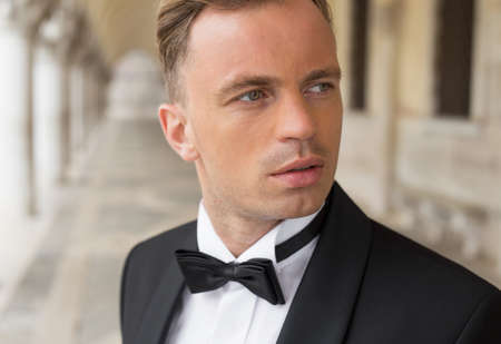 Portrait of confident sexy man in tuxedo and bow tie