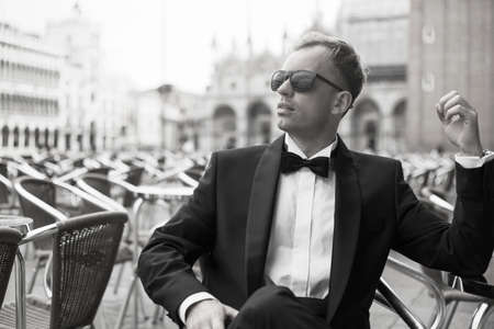 outdoor photo: Black and white photo of handsome man in tuxedo