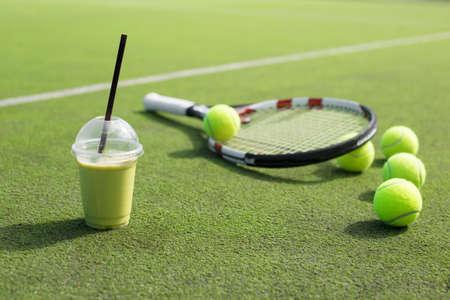 raqueta de tenis: batido de color verde y la raqueta de tenis y pelotas en la cancha Foto de archivo
