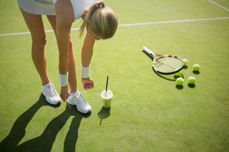 court shoes: Tennis player tying shoes on the court