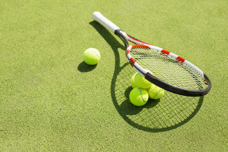racket: Tennis racket and balls on the court grass Stock Photo
