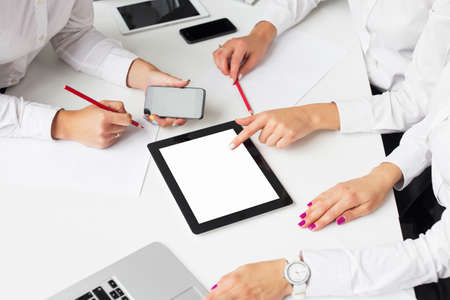 blank screen: Business women using tablet computer at the meeting