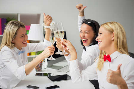 fun at work: Happy women colleagues drinking champagne in the office