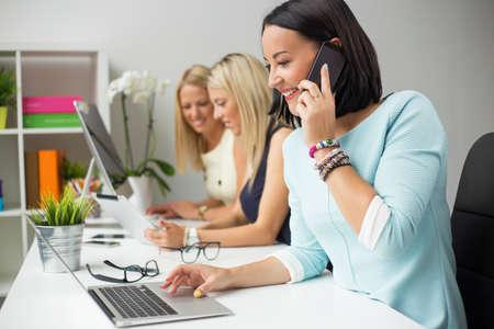 創造的な女性の同僚がオフィスで働く