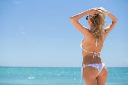 niñas en bikini: Mujer en bikini mirando en la distancia en la playa