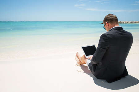 Businessman with computer on the beach