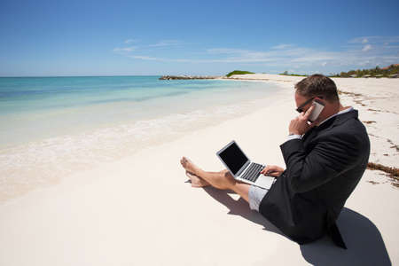 Businessman on the beach working with computer and speaking on phone