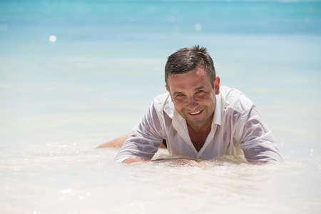 Handsome man having fun in wet shirt