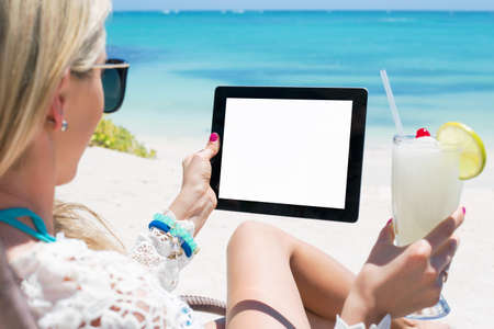 tablet computer: Relaxed woman drinking cocktail and holding tablet computer on the beach Stock Photo