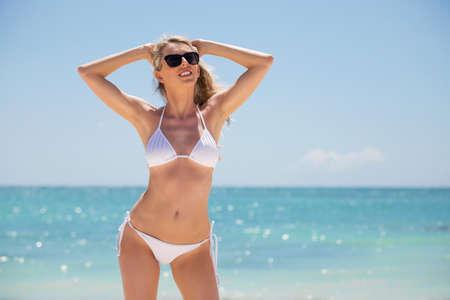 Frau im weißen Bikini posiert am Strand