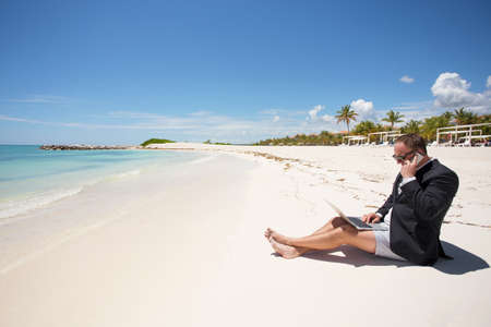 busy: Busy businessman working on the beach Stock Photo