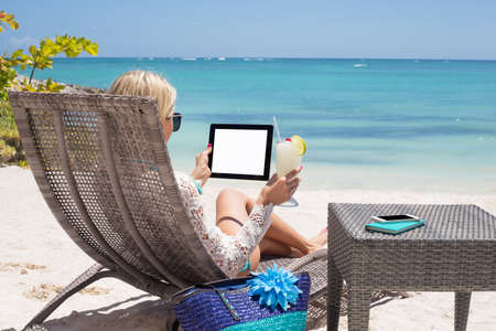 relaxed: Woman using digital tablet on the beach