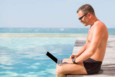 anywhere: Young man using laptop computer by the pool