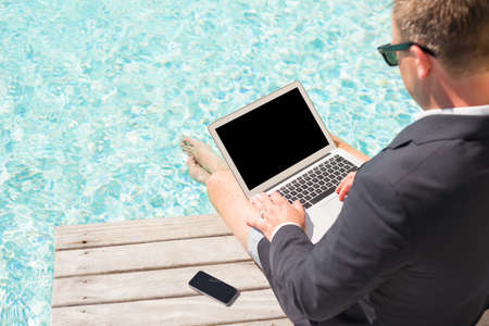 freedom concept: Business man sitting by the pool and working with laptop computer