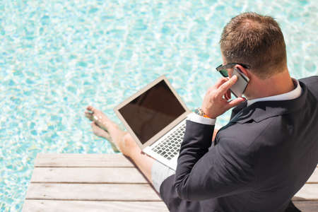 anywhere: Businessman using computer and speaking on phone by the pool Stock Photo