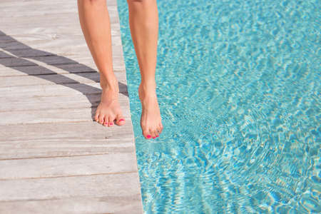 bare body women: Woman with bare feet by the pool Stock Photo