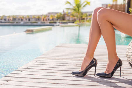 Woman in black high heel shoes sitting outdoors by the pool Stock Photo