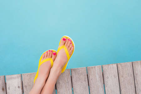 flops: Woman with yellow flip flops by the pool