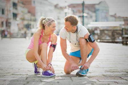 correr: Mujer y hombre atar los zapatos de los deportes antes del entrenamiento Foto de archivo