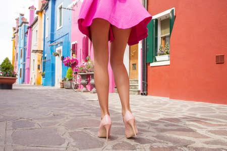 piernas con tacones: La mujer llevaba zapatos de tacón alto y mini falda