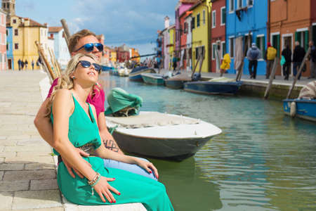 jumpsuit: Tourists couple visiting Burano island of Venice in Italy Stock Photo
