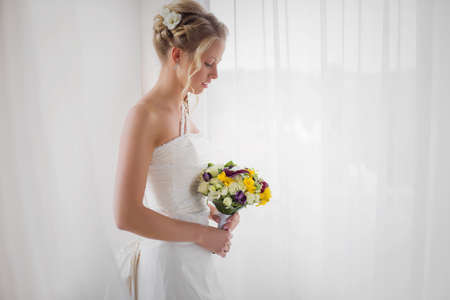 nude bride: Bride standing by the window with flowers in her hand
