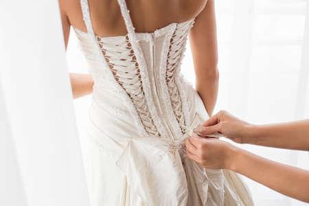 hochzeit: Helfende Braut mit einem Kleid