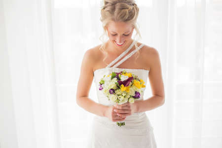 Bride looking down at her flowers